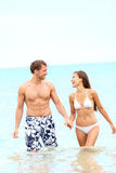 Couple on beach walking in water. Holding hands having fun during summer holidays travel vacation. Young happy joyful interracial couple, Caucasian man, Asian Stock Photography