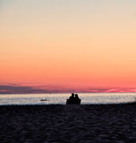 Couple at Beach Watching Sunset Royalty Free Stock Photography