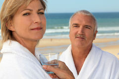 A couple at the beach wearing bathrobes Stock Photo