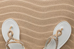 Couple beach white flip flops encrusted with rhinestones standing on the sand. With space for your text Royalty Free Stock Photography