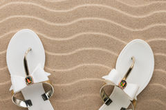 Couple beach white flip flops encrusted with rhinestones standing on the sand. With space for your text Stock Images