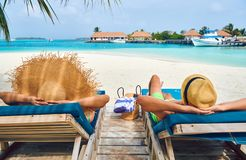Couple at beach on wooden sun bed loungers. Young couple at beach on wooden sun bed loungers. Summer vacation at Maldives stock image
