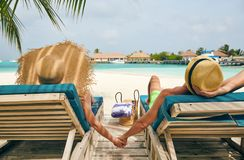 Couple at beach on wooden sun bed loungers. Young couple at beach on wooden sun bed loungers. Summer vacation at Maldives stock photos
