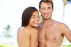 Couple beach - young multicultural people. Happy young interracial couple smiling happy looking at camera. Young asian women and Caucasian men during summer Stock Image