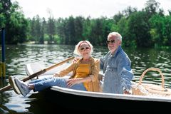 Couple of beaming elderly man and woman feeling satisfied after river trip. Satisfied couple. Couple of beaming elderly men and women wearing sunglasses feeling stock images