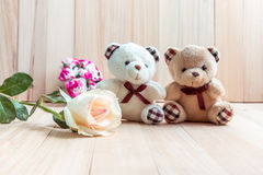 Couple bear sit near Pastel rose, wood background Royalty Free Stock Images