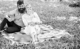 Couple bearded man and blonde woman relax nature while sit on green grass meadow. Relax and inspiration concept. Couple royalty free stock photography