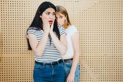 A couple of beautiful girlfriends against a yellow wall background. royalty free stock photography
