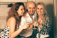 Couple of beautiful ladies having fun with a guy at a party with Stock Photography
