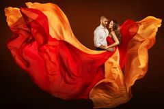 Couple Beauty Portrait, Man and Dreaming Woman in Waving Dress as Flame on Wind stock images