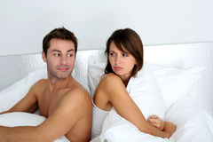 Couple in bed. Couple sitting back to back in bed, arguing Stock Photography
