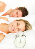 Couple in bed with alarm clock Stock Photo