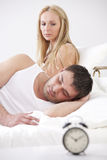 Couple in bed with alarm clock Stock Image