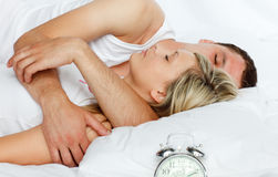 Couple in bed with alarm clock going off Stock Image