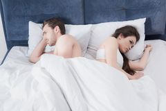 Couple in bed after argument. Depressed couple in bed after argument looking at different sides stock photography