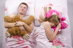 Couple in bed asleep with soft toys Stock Photos