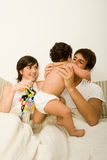 Couple in bed with baby Stock Images