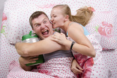 Couple in bed: he with a barrel of beer, she tries to take away Royalty Free Stock Photos