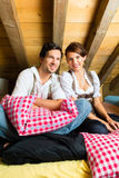 Couple with bed clothes in mountain cabin Stock Images