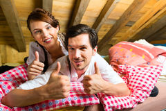 Couple with bed clothes in mountain cabin Stock Image