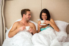 Couple in bed with cups. Stock Photo