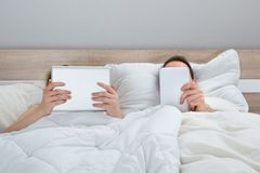 Couple in bed with digital tablets Royalty Free Stock Photos