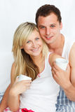 Couple in bed drinking coffee and smiling Royalty Free Stock Photo