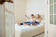 A couple in bed is having breakfast, watching TV, reading a book. In the bedroom Royalty Free Stock Photography