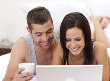 Couple in bed having fun with a laptop Stock Images