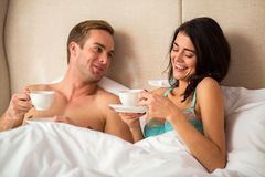 Couple in bed holding cups. Smiling women in bra. You impress me every day Royalty Free Stock Photos