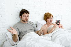 Couple in bed husband frustrated upset and unsatisfied while his internet addict wife is using mobile phone Royalty Free Stock Photos