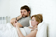 Couple in bed husband frustrated upset unsatisfied while wife using mobile phone Royalty Free Stock Image