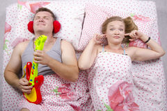 The couple in the bed-husband plays guitar, wife covered her fingers in his ears Stock Photos