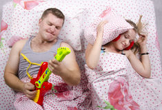 The couple in the bed-husband plays guitar, wife covered her pillow Royalty Free Stock Photo