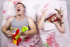 The couple in the bed-husband plays guitar, wife covered her pillow Royalty Free Stock Photos