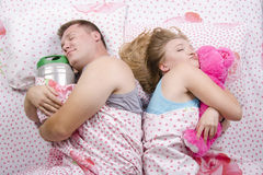 The couple in the bed-husband sleeps with a barrel of beer, a wife with a soft toy Royalty Free Stock Photo