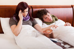 Couple in bed, ill. Young couple lying in bed, ill Royalty Free Stock Images