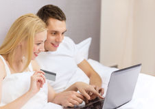 Couple in bed with laptop computer and credit card Stock Images