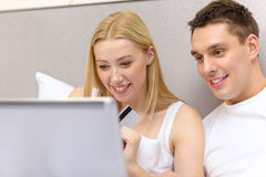 Couple in bed with laptop computer and credit card Royalty Free Stock Photos