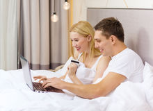 Couple in bed with laptop computer and credit card Stock Photos