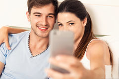 Couple on bed making selfies Stock Photography