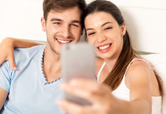 Couple on bed making selfies Stock Image