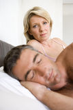 Couple on bed, man asleep in foreground, portrait of woman in background Stock Photo