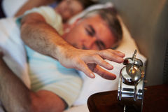 Couple In Bed With Man Reaching To Switch Off Alarm Clock Royalty Free Stock Photography