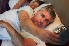 Couple In Bed With Man Reaching To Switch Off Alarm Clock Stock Image