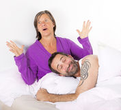 Couple in bed. Man is sleeping and smiling and women is upset Royalty Free Stock Image
