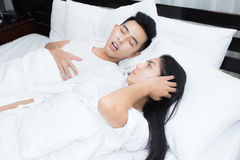 Couple in bed, man snoring on the bed in the bedroom. Couple in bed, men snoring on the bed in the bedroom and women can not sleep Stock Photography
