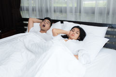 Couple in bed, man snoring on the bed in the bedroom. Couple in bed, men snoring on the bed in the bedroom and women can not sleep Stock Images