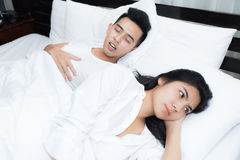 Couple in bed, man snoring on the bed in the bedroom. Couple in bed, men snoring on the bed in the bedroom and women can not sleep Royalty Free Stock Images