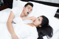 Couple in bed, man snoring on the bed in the bedroom. Couple in bed, men snoring on the bed in the bedroom and women can not sleep Royalty Free Stock Image